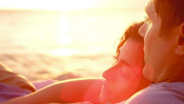 A young couple in love laying on a beach watching the sunset Royalty-free stock video
