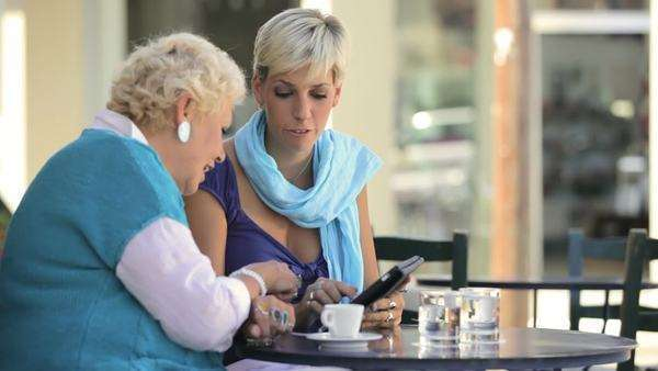 An younger woman sits at a table and shows a older woman how to use a tablet Royalty-free stock video