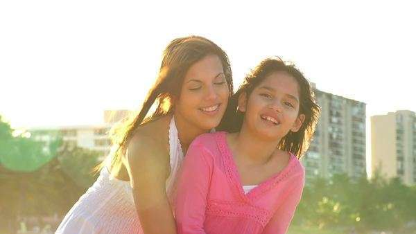A mother and daughter smile for the camera while at the beach Royalty-free stock video