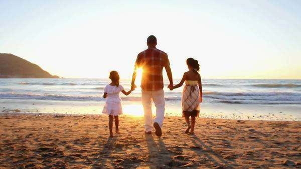 A father with girls walk and hold hands up to the surf on a beach in Mexico Royalty-free stock video