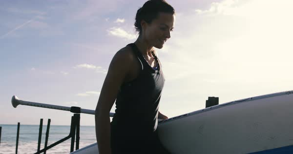 Female walking with paddle board on the beach Royalty-free stock video