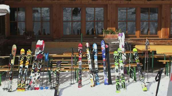 Arranged ski and ski poles outside wooden house Royalty-free stock video