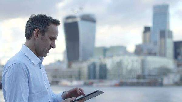 Business man uses his digital tablet/ipad in the city Royalty-free stock video
