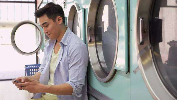 A Young Man sits with his smartphone in a Launderette, medium shot Royalty-free stock video