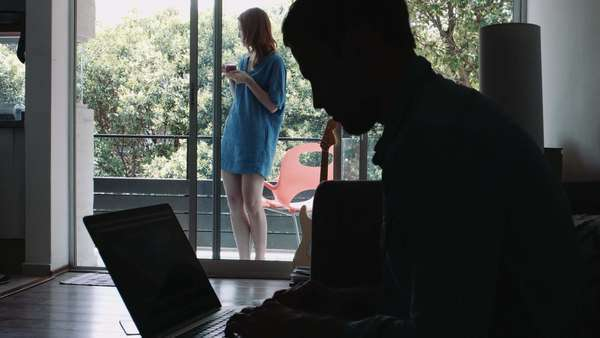 Young woman holding cup of black tea and man using laptop Royalty-free stock video