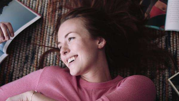Young woman lying on rug and playing with her hairs, laughing Royalty-free stock video
