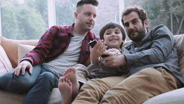 Same sex couple family watching TV on sofa Royalty-free stock video