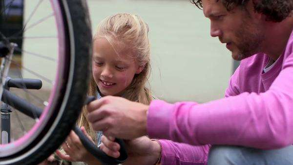 Father and daughter inflating bicycle tyre Royalty-free stock video