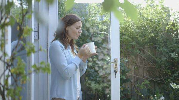 Woman drinking coffee outside home Royalty-free stock video