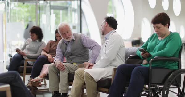 Senior male talking to doctor in a crowded hospital waiting room  Royalty-free stock video