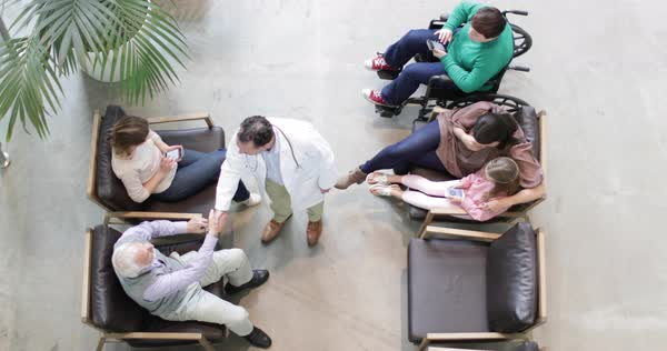 Overhead shot of medical doctor greeting senior male in waiting room Royalty-free stock video