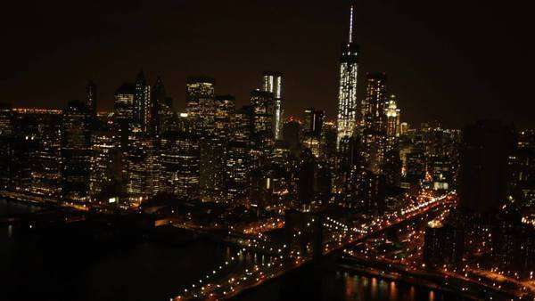 Aerial view over Brooklyn Bridge and Manhattan cityscape at night. Royalty-free stock video