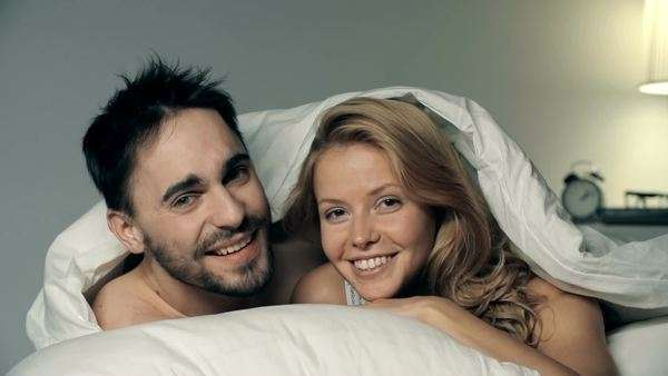 Close up of couple cuddling under the sheets and looking at camera Royalty-free stock video