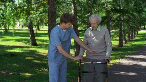Close up of medical worker instructing senior patient to use walker correctly Royalty-free stock video