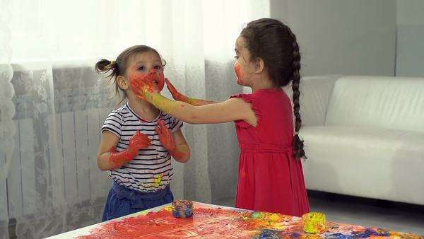 Two girls smudging paint on their faces for fun Royalty-free stock video