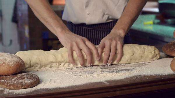 Mid-section of cropped unrecognizable chef kneading long piece of dough Royalty-free stock video