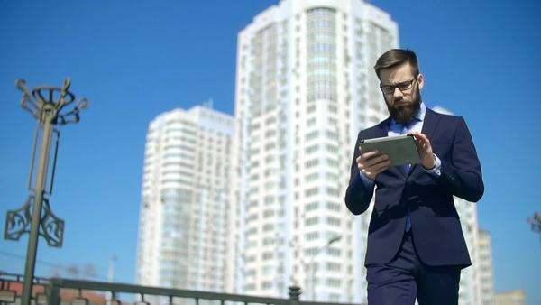 Smart businessman approaching camera walking along the street and browsing touchpad Royalty-free stock video