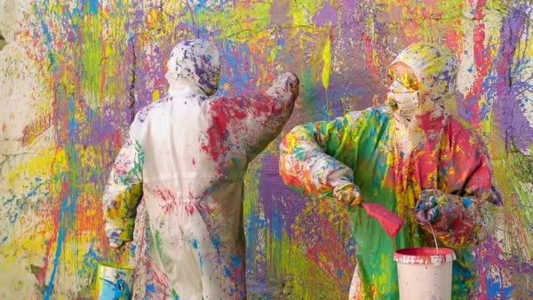 Two artists in paint-splatter protective coveralls splashing around multi-colored paint and creating abstract mural Royalty-free stock video