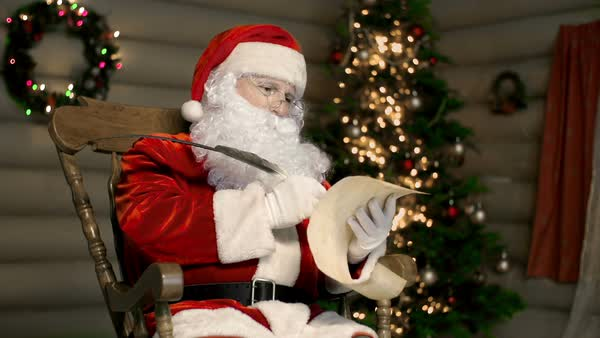 Santa Claus reading a list and making notes in it with a feather pen  Royalty-free stock video