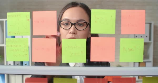 Young businesswoman reading sticky note reminders and removing them from glass wall  Royalty-free stock video
