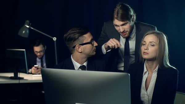 Business professional explaining his colleagues information on the computer screen; man in the background using his mobile phone Royalty-free stock video