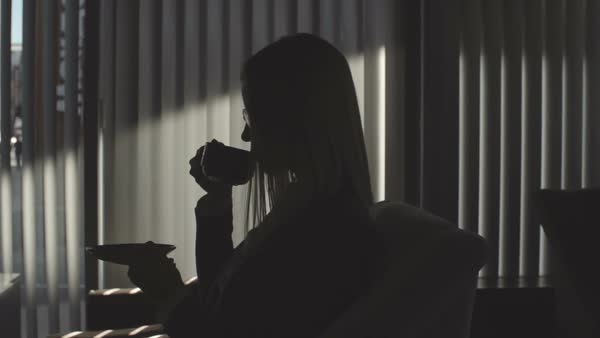 Business woman drinking coffee and using her smartphone in the dark office Royalty-free stock video