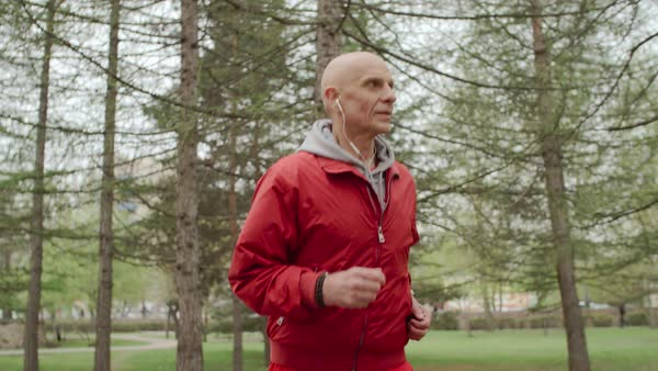 Senior man running in the park and listening to music on headphones Royalty-free stock video