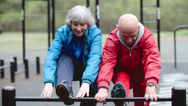 Senior man and woman stretching their legs on the playground Royalty-free stock video