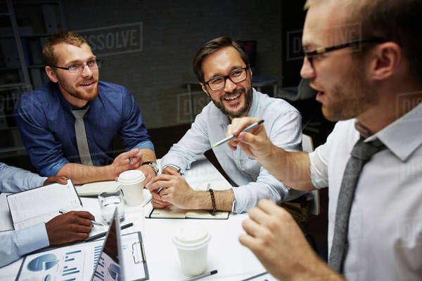 Businessmen communicating in office till late evening Royalty-free stock photo