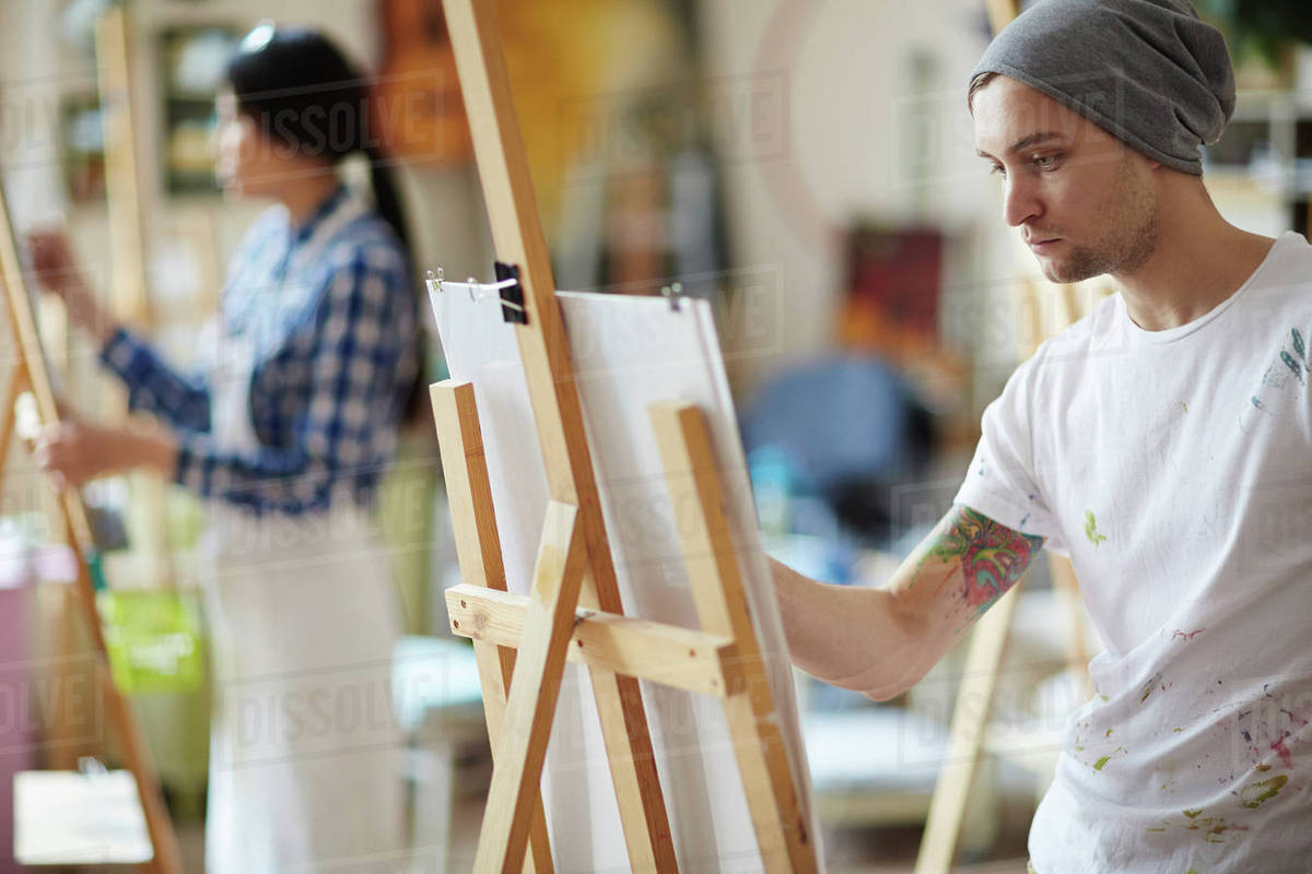 767d1ea5ad6 Male artist dressed in beanie hat and white shirt covered in colorful paint  sketching on easel in brightly lit studio with blurred female artist in  apron in ...