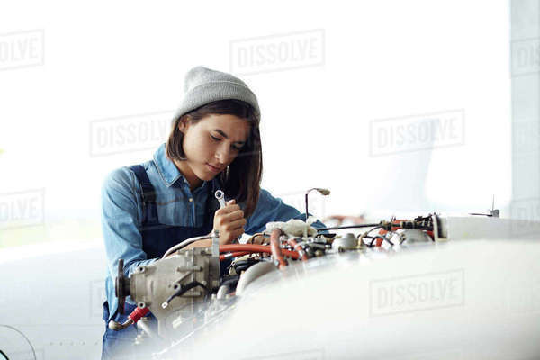 Young woman repairing air jet engine Royalty-free stock photo