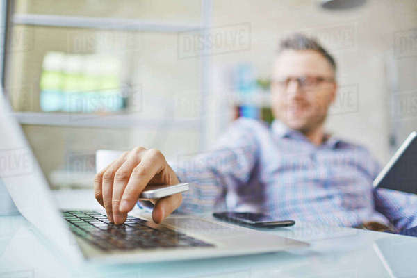 Hand of man with cellphone pressing laptop key Royalty-free stock photo