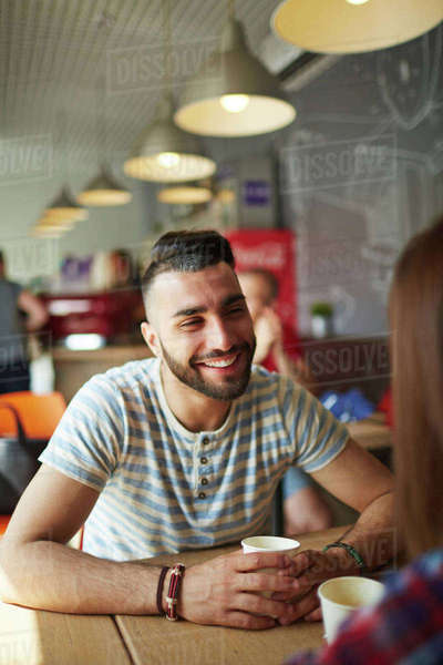 Happy guy talking to girlfriend by coffee Royalty-free stock photo