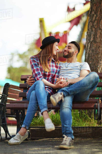 Young man and woman talking on bench in park Royalty-free stock photo