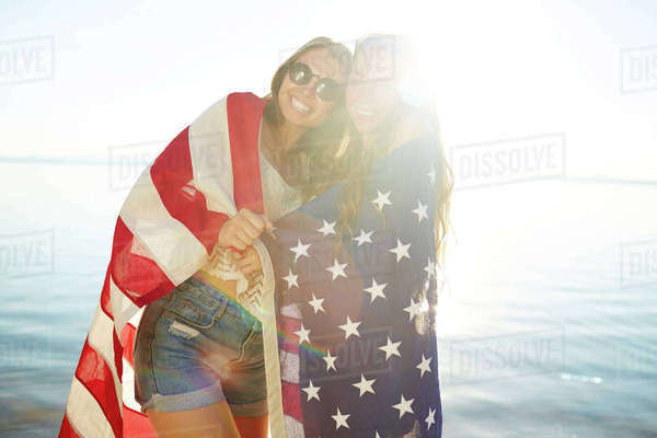 Two pretty girls wrapped in national American flag looking at camera on sunny day Royalty-free stock photo