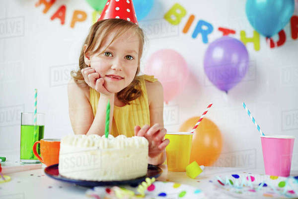 Cute girl looking at camera by birthday cake Royalty-free stock photo