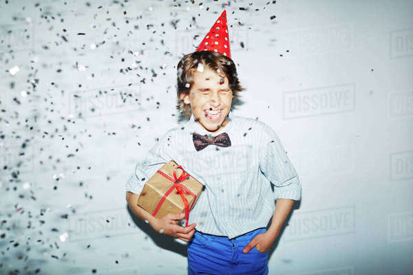 Ecstatic boy with packed birthday gift standing in confetti fall Royalty-free stock photo