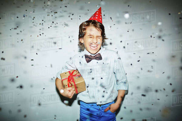 Cheerful boy in birthday cap holding box with gift Royalty-free stock photo