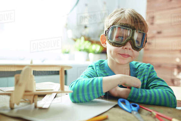 Cute boy in pilot goggles sitting by table Royalty-free stock photo