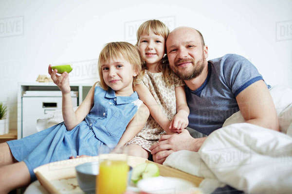 Happy family of father and two daughters looking at camera Royalty-free stock photo