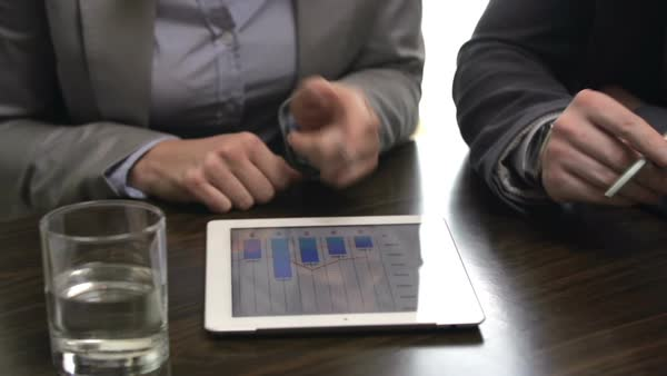 Dolly of three unidentified business partners in boardroom discussing financial stats, using digital tablet and putting down information in handwriting Royalty-free stock video