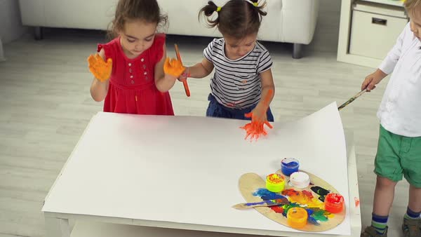 Kids playing together leaving palm prints on the sheet of paper Royalty-free stock video