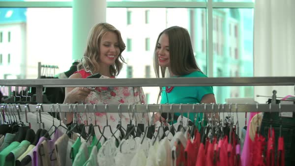 Close up of two girlfriends discussing clothes in apparel department Royalty-free stock video
