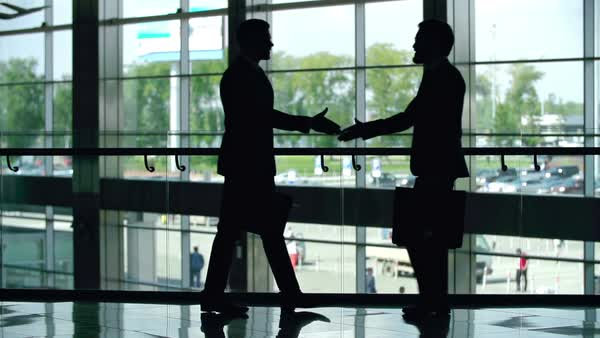 Silhouettes of two businessmen greeting each other with a handshake Royalty-free stock video