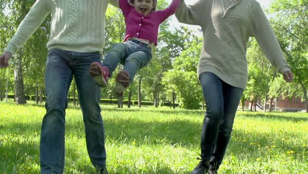 Slow motion of kid running with parents and jumping holding their hands Royalty-free stock video