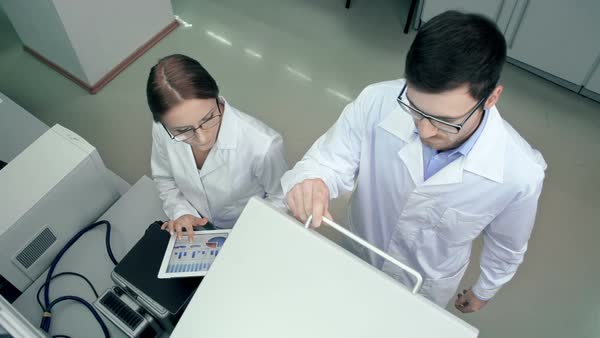 Above view of two lab colleagues testing pharmaceutical sample using centrifuge Royalty-free stock video