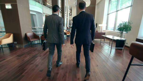 Camera following two businessmen walking along hotel lobby and discussing issues Royalty-free stock video