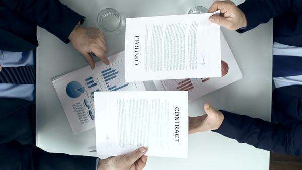 Direct from above view of two business parties signing respective copy of a contract and congratulating each other with firm handshake Royalty-free stock video