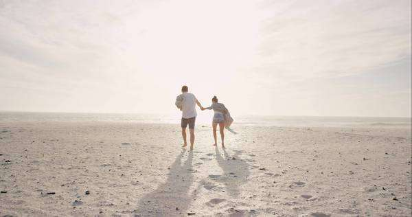 Young couple holding hands walking towards sunset on empty beach woman leading man on romantic vacation Royalty-free stock video