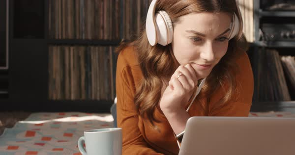 Beautiful woman listening to music on laptop at trendy home with headphones drinking coffee smiling vintage records in background orange retro colours and styling Royalty-free stock video